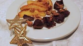 Braune Fleischstücke auf einem weißen Teller im Halbkreis angeordnet, dahinter goldgelbe Apfelspalten im Halbkreis angeordnet, als Dekoration zwei goldene Sterne am Tellerrand (Foto: SWR, SWR - Karin Hässelbarth)