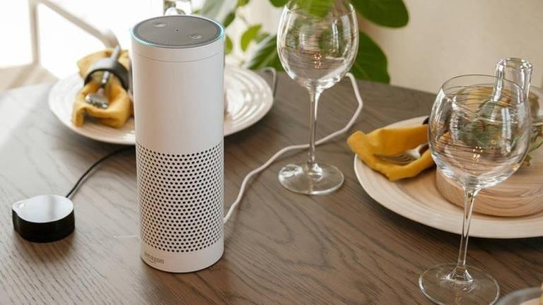 Smarter Lautsprecher steht auf gedecktem Tisch