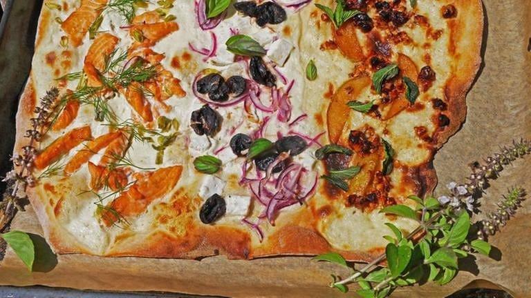 Flammkuchen dreigeteilt mit Lachs, mit roten Zwiebeln und mit früchten und Minze auf backpapier (Foto: SWR, Stefanie Kühn -)