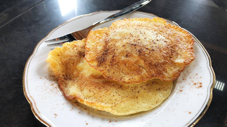 zwei Apfelpfannkuchen auf einem weißen Teller mit Goldrand (Foto: SWR, Deborah Kölz)