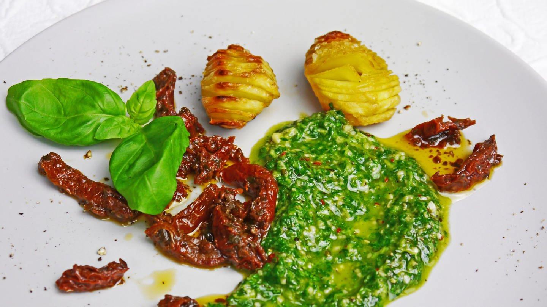weißer Teller mit getrockneten Tomaten, grünem Hanf-Pesto und eingeritzten Kartoffeln