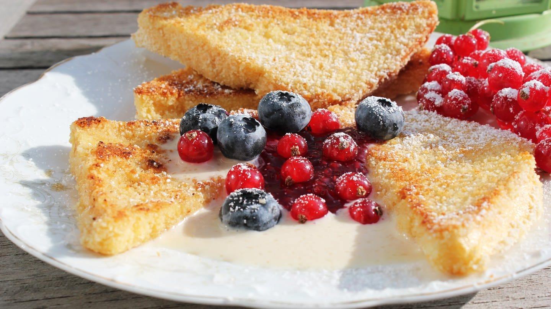 3 panierte, gebratene Brotdreiecke mit verschiedenen Beeren in der Mitte auf einem weißen Teller (Foto: SWR, Imogen Voth)