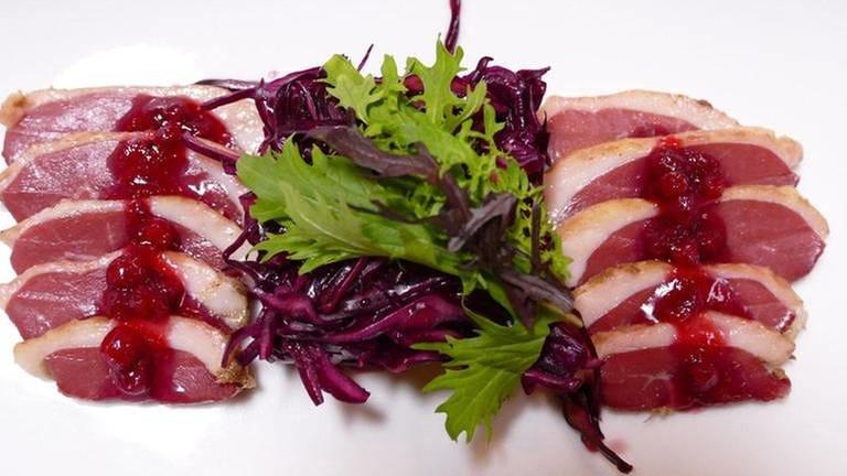 Scheiben von rosa gebratener Ente mit roten beeren mit Salat (Foto: SWR, Eva Eppard -)