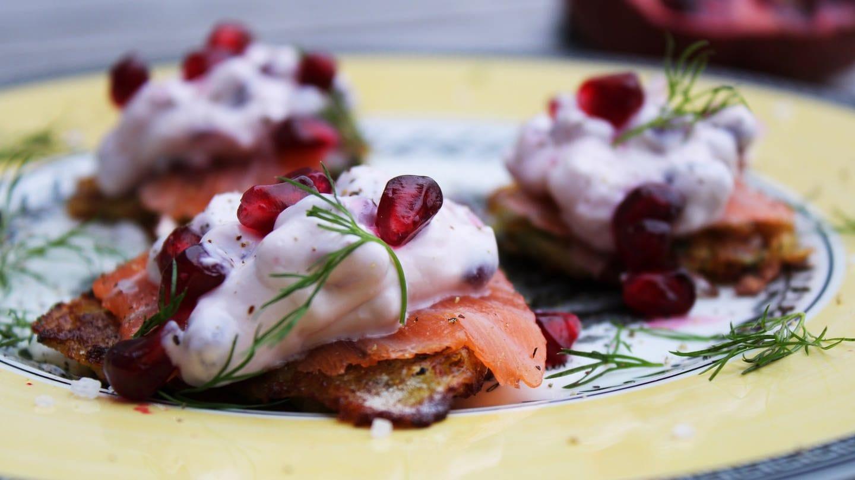 kleine Reibekuchen mit Lachsscheibe und Granatapfelkernen darauf auf gelbem Teller mit etwas Dill (Foto: SWR, Imogen Voth)
