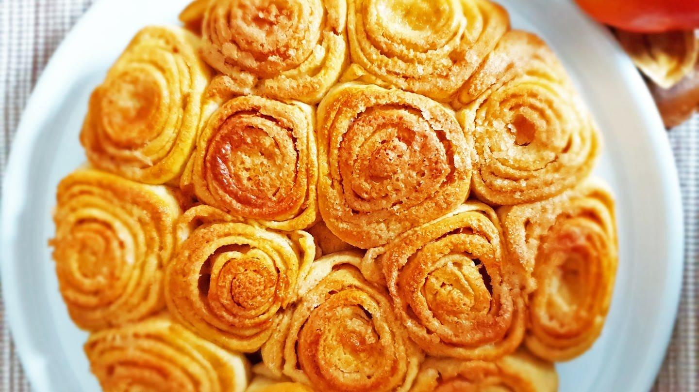 Apfel-Zimtschnecken in einer Runde wie eine Torte auf einer Platte angeordnet