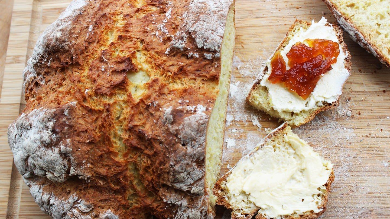 knuspriges Brot, halb aufgeschnitten mit zwei Scheiben mit Butter und Marmelade daneben
