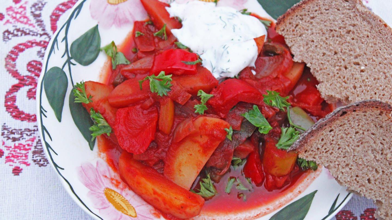 Teller mit Blumenmuster, darauf vegetarisches Gulasch mit Paprika und Kartoffeln, dazu helle Creme und zwei Scheiben Brot (Foto: SWR, Imogen Voth)