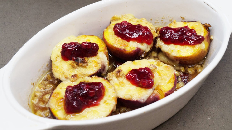 weiße Auflaufform mit halben Pfirsichen mit Käse überbacken und je einem Klecks rotem Gelee