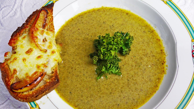 Grünkohlsuppe im Teller, auf dem Rand ein Stück Brot mit Käse überbacken (Foto: SWR, Stefanie Kühn)