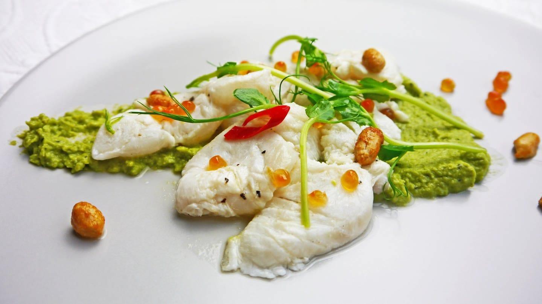 weißer Teller mit grünem Erbsenpüree, darauf helle Fischstücke mit Chili, Nüssen und hellrosa Lachskaviar dekoriert (Foto: SWR, Stefanie Kühn)