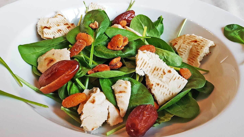 weißer großer Teller mit Spinatsalat mit Datteln, Mandeln und Fladenbrotstücken (Foto: SWR, Stefanie Kühn)