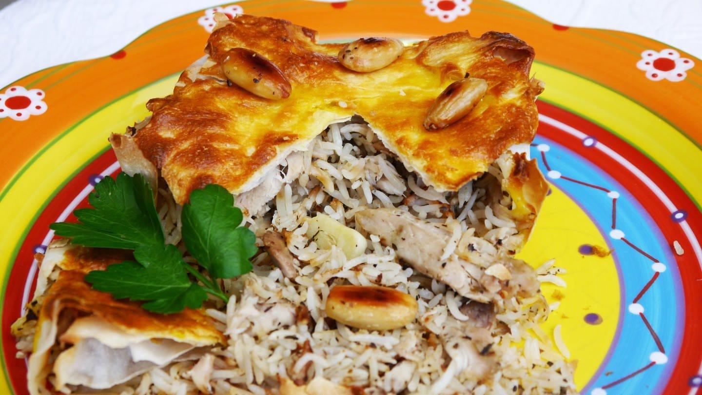 braungebackene Teigtasche, aufgeschnitten, mit Reisfüllung mit Huhn und Mandeln auf einem bunten Teller (Foto: SWR, Stefanie Kühn)