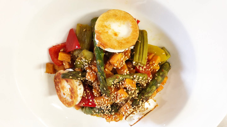 weiße Schüssel mit Salat aus grünem Spargel, roter Paprika, Möhren und einer Scheibe Ziegenkäse