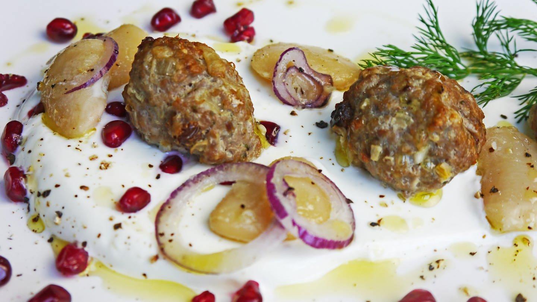 Hackfleischbällchen mit dicken, weißen Bohnen und roten Zwiebeln auf weißer Creme mit Cranberries