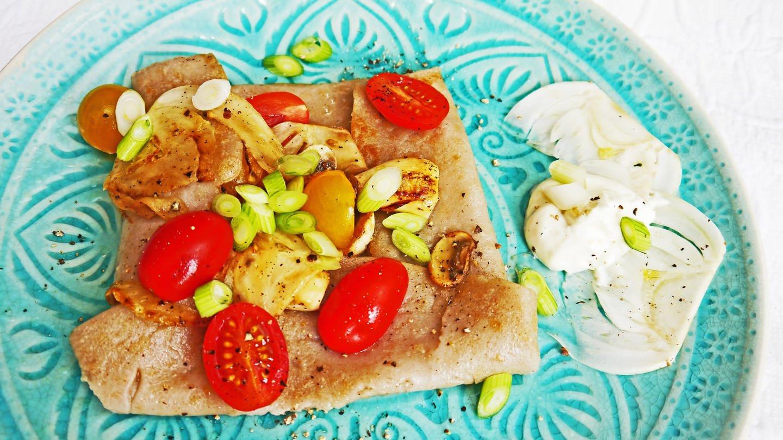 blauer Teller mit einem Teigfladen mit Tomaten, Pilzen und Frühlngszwiebeln darauf (Foto: SWR, Stefanie Kühn)