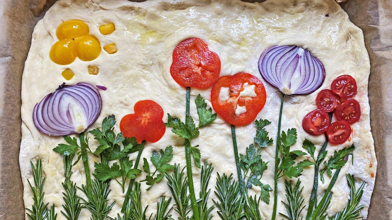ungebackener Hefeteig auf Backblech mit Gemüse, das wie Blumen arrangiert ist.