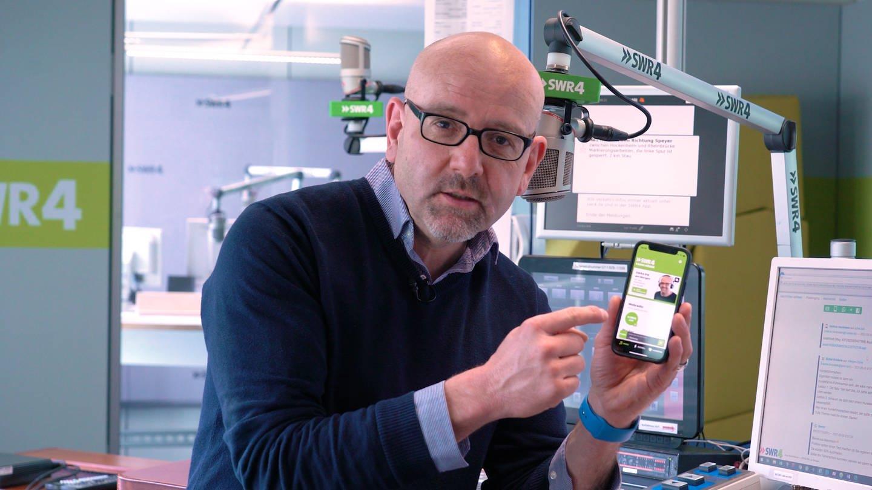 SWR4 Moderator Jörg Assenheimer hält im Hörfunkstudio ein Smartphone in der Hand und erklärt die SWR4 App