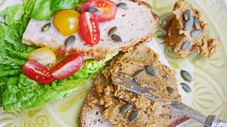 zwei halbe Brotscheiben mit einem Salatblatt und kleinen Tomaten und einem rötlichen Brotaufstrich mit einem verzieren Messer