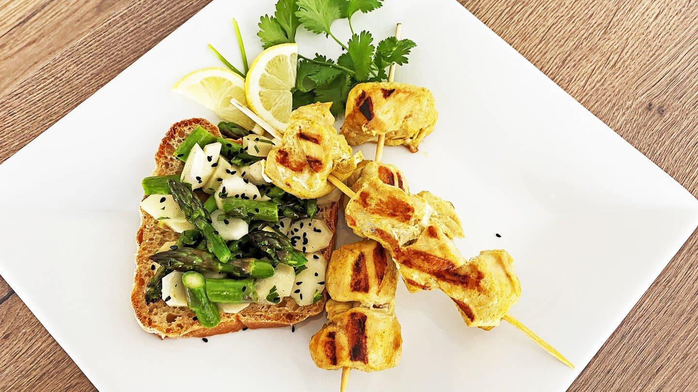 Spargelsalat auf Toast mit Hühnerspießen als Snack für ein Buffet