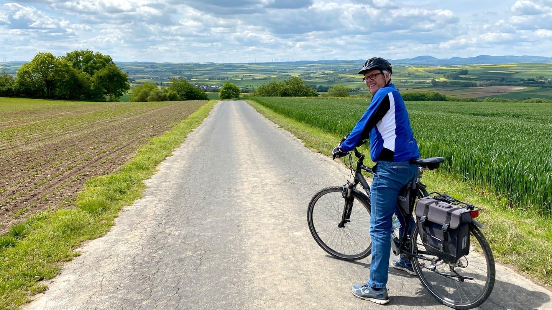 Ein Radfahrer schaut mit Blick nach hinten in die Kamera