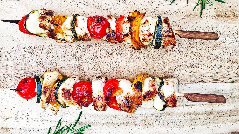 Holzbrett mit zwei Spießen mit gegrillten Hühnchenwürfeln, Tomaten. Zucchini und Rosmarin daneben