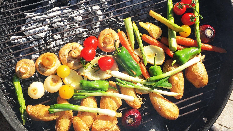 verschiedenes Gemüse, wie Tomaten, Zucchini, Spargel, Pilze, Zwiebeln und Kartofeffeln auf einem Grillrost