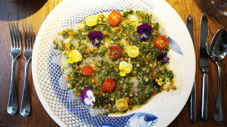 gemusterter Teller mit Salat mit Kräuter-Vinaigrette mit Blumen als Deko
