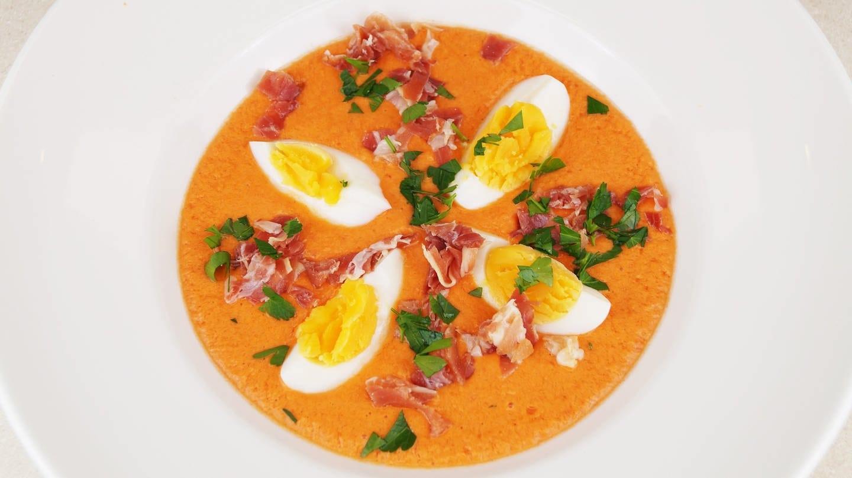 weißer Teller mit orange-heller Tomatensuppe mit Eiervierteln als Einlage