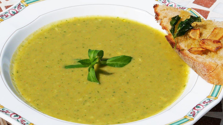 weißer Teller mit grüner Suppe mit Kräutern als Deko und mit einem Stück getoastetem Brot auf dem Tellerrand