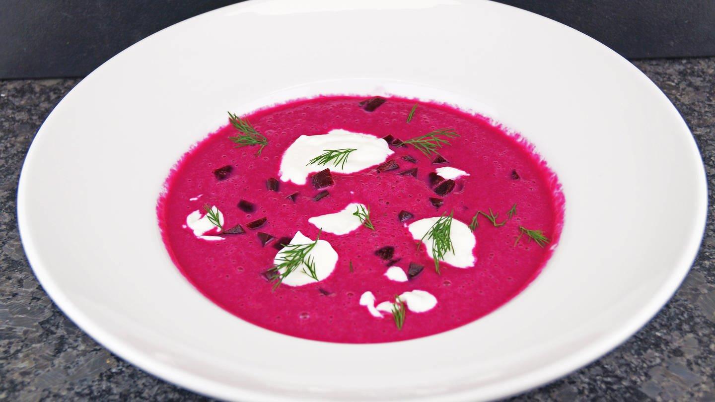 weißer Suppenteller mit rosa rote-Bete-Suppe mit hellen Käsetücken darin und Nusstückchen und Dill darübergestreut