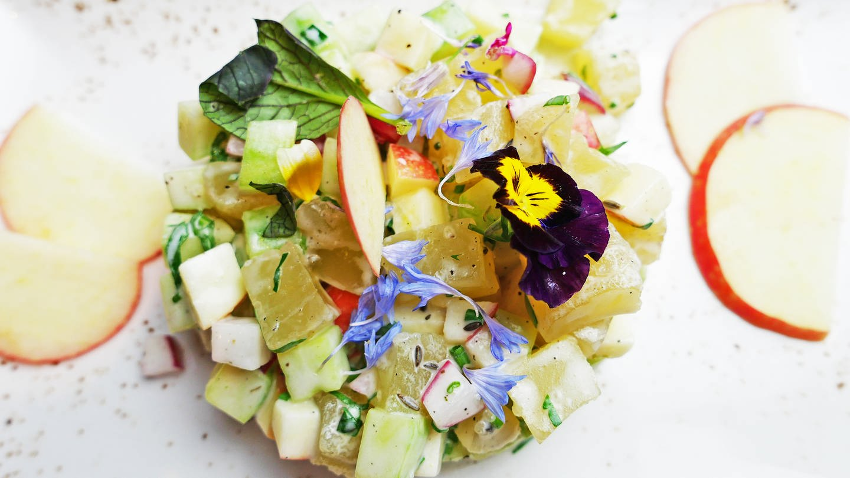 Tatar aus Handkäse mit Gurkenstückchen und Blumen als Deko