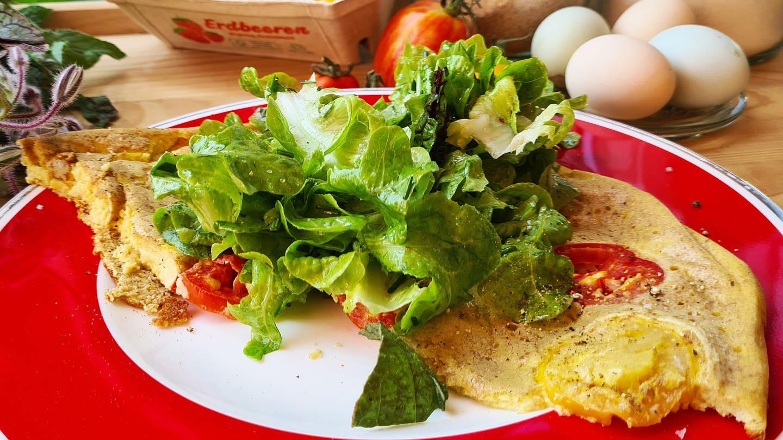 Rührei mit Tomaten darin, dazu Salt, im Hintergrund Eier und Tomaten