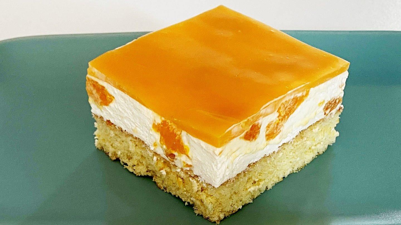 ein eckiges Stück Kuchen mit braunem Boden, heller Creme und orangem Guss