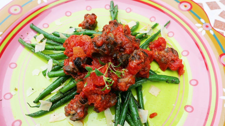 bunter Teller mit grünen Bohnen und Schnecken in Tomatensoße mit Parmesanhobel