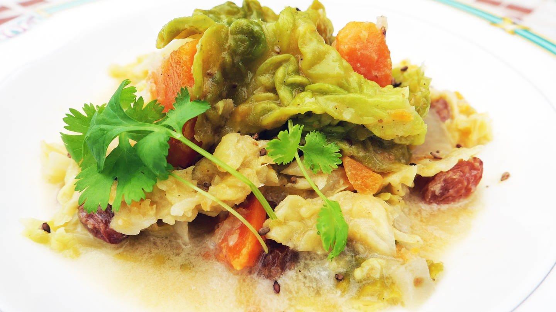 Eintopf mit Wirsing und Süßkartoffeln und Sesamkörnern auf einem weißen Teller