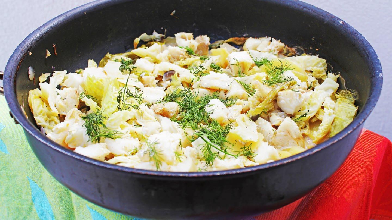 schwarzer Topf mit einer Mischung aus Fischstücken, Kartoffeln und Wirsing mit Dill