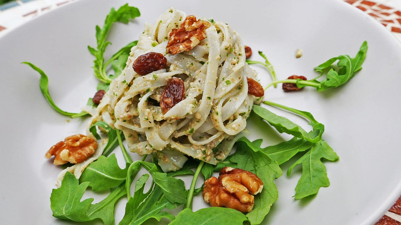 helle Bandnudeln mit Walnuss-Pesto, Walnüssen und getrockneten Beeren auf Rucola-Blättern