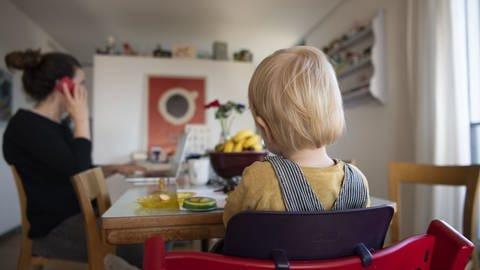 Eine Frau sitzt im Homeoffice an ihrem Laptop und telefoniert, während ihr Kind neben ihr in einem Kinderstuhl am Tisch sitzt. (Foto: dpa Bildfunk, picture alliance/Christian Beutler/KEYSTONE/dpa)
