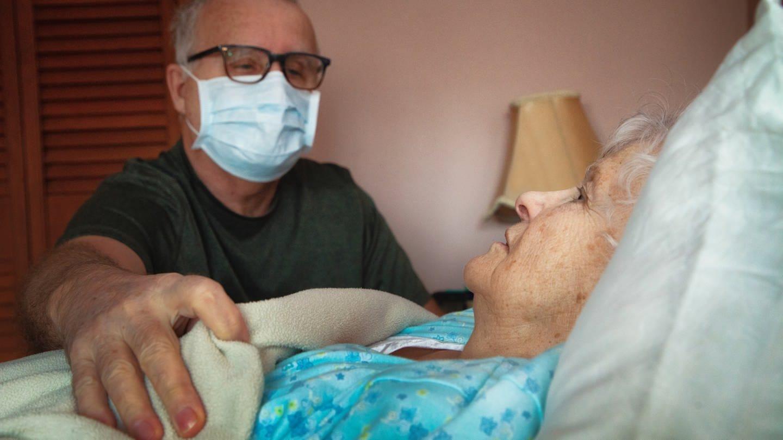 Ein Senior legt besorgt seine Hand auf seine kranke Partnerin. (Foto: Getty Images, Nicolas McComber)