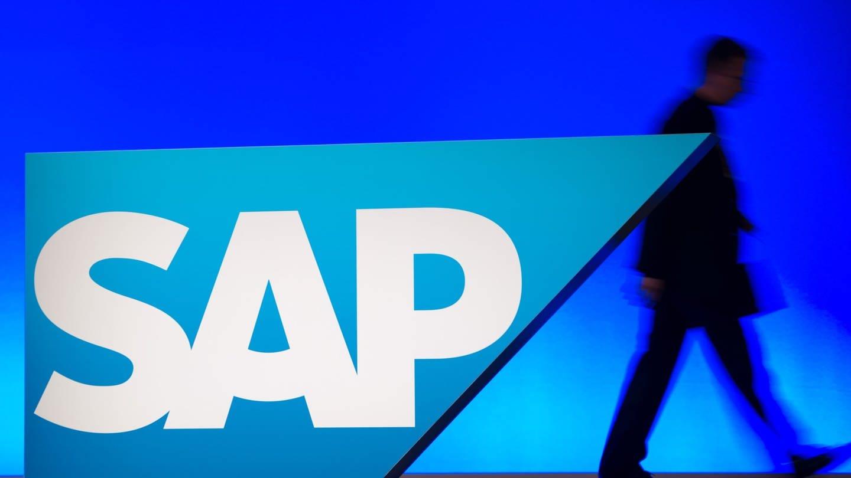Ein Mitarbeiter geht in Mannheim in der SAP-Arena bei der SAP-Hauptversammlung an einem Logo des Konzerns vorbei.