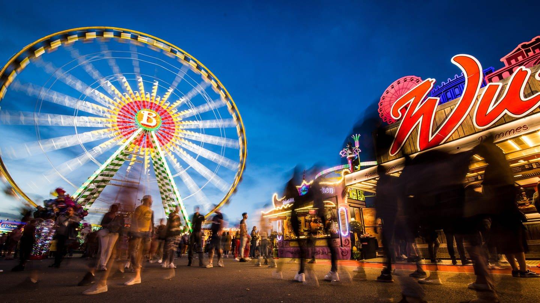 Besucher genießen zur blauen Stunde das 81. Stuttgarter Frühlingsfest auf dem Cannstatter Wasen.