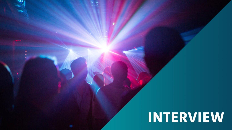 Menschen in einem Club tanzen, ein Scheinwerfer strahlt fächerförmiges Licht in die Kamera