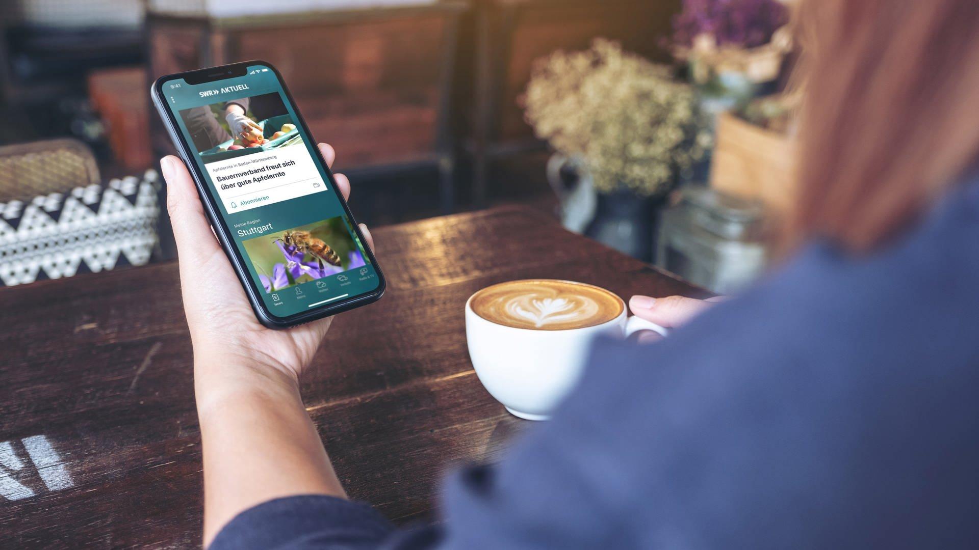 Eine Frau trinkt Kaffee und schaut in die Timeline der SWR Aktuell App