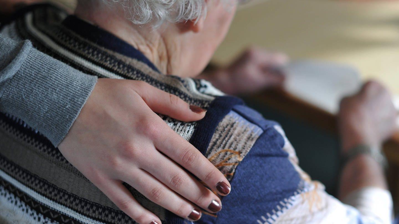 Eine junge Frau hat ihre Hand auf der Schulter einer älten Frau gelegt, die in einem Seniorenheim am Tisch sitzt. (Foto: dpa Bildfunk, picture alliance/Patrick Pleul/dpa-Zentralbild/dpa)
