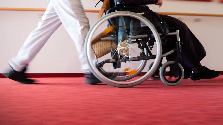 Ein Pfleger eines Pflegeheims schiebt eine Bewohnerin mit einem Rollstuhl. (Foto: dpa Bildfunk, picture alliance/Tom Weller/dpa)