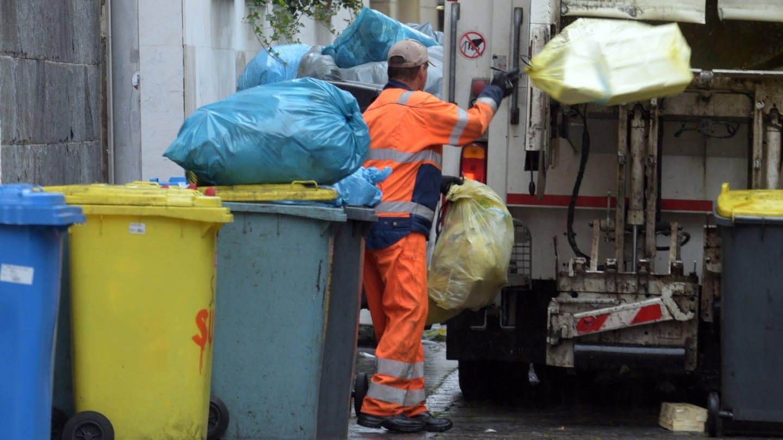 Ein Mitarbeiter der Entsorgungsbetriebe wirft Abfall in ein Müllfahrzeug (Foto: dpa Bildfunk, picture alliance/Stefan Puchner/dpa)