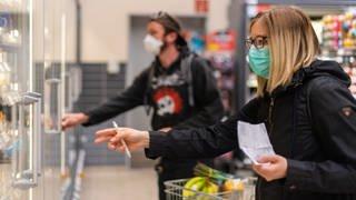 Kunden gehen in einem Supermarkt einkaufen und tragen dabei Mund-und-Nasen-Schutz. (Foto: dpa Bildfunk, Robert Michael/dpa-Zentralbild/dpa)