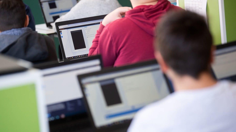Schülerinnen und Schüler nehmen im Klassenzimmer am Unterricht mit Hilfe von Laptops und Tablets teil.