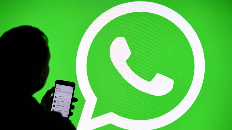 Ein Mann mit Smartphone steht vor einem Monitor mit dem Logo des Messenger-Dienstes WhatsApp. (Foto: dpa Bildfunk, picture alliance/Carsten Rehder/dpa (Symbolbild))