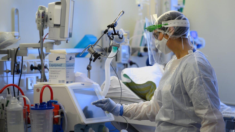 Symbolbild: Eine Intensivpflegerin ist im Schutzkleidung auf der Covid-19 Intensivstation in der VAMED Klinik Schloss Pulsnitz mit der Versorgung von Corona-Patienten beschäftigt. (Foto: dpa Bildfunk, picture alliance/dpa/dpa-Zentralbild | Robert Michael)